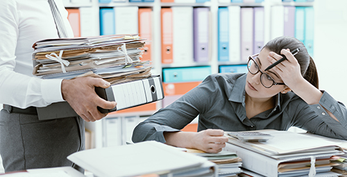 Young woman surrounded by paper work