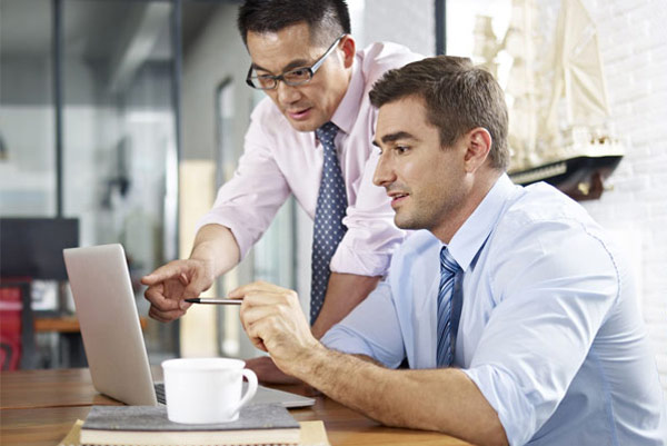 men leaning over laptop, business meeting, tax free benefits for expats in china